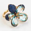 Лепестки выполнены из голубых топазов и украшены синими сапфирами и бриллиантами.